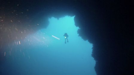 divers through the blue hole