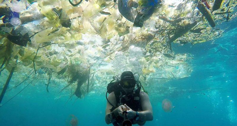 Un plongeur se filme dans la mer à Bali entouré de plastique